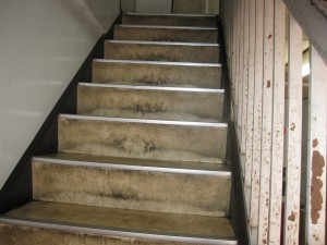 a staircase and a hand railing needing renovation